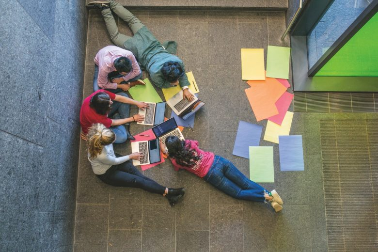 Overhead view of students working on a coding project.