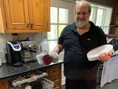 Stuart Diamond loads a dishwasher