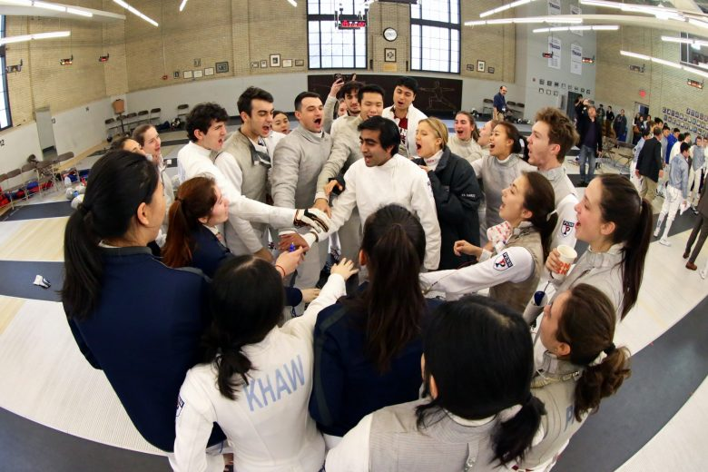 Group of Penn Fencers gather together with hands in before match