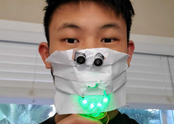 """Student models DIY paper facemask with sensors and green LED lights in shape of a """"smile"""""""