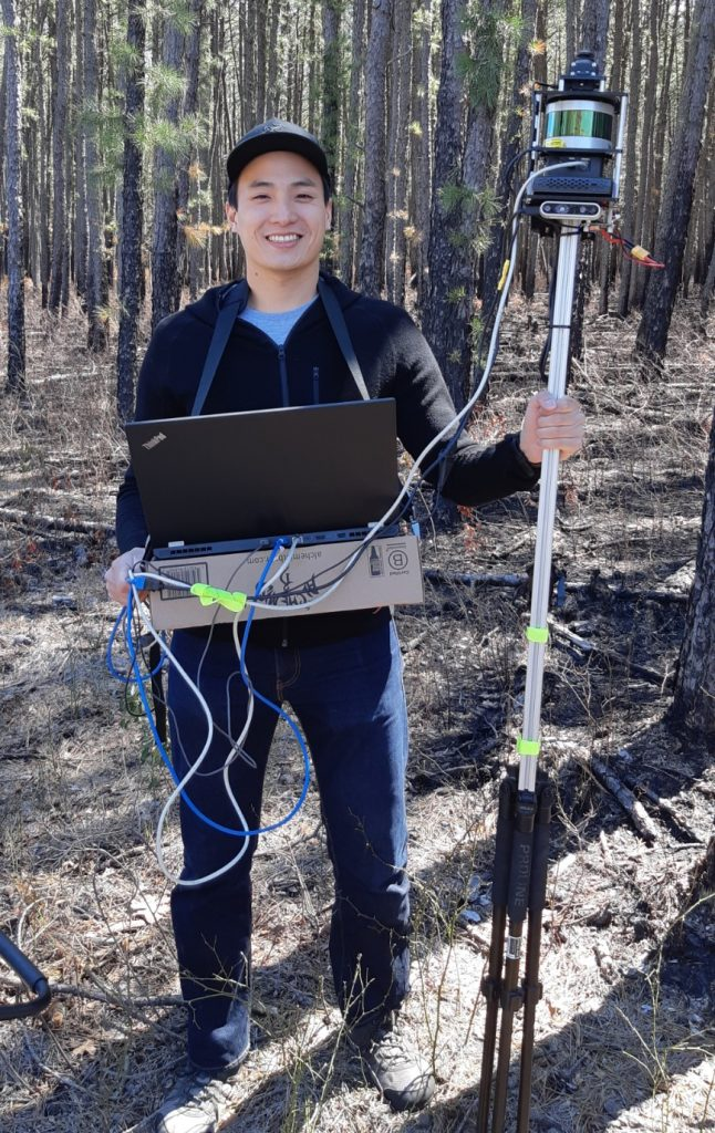 Steven Chen in a forest, wearing a laptop in a harness and holding a sensor on a tall pole.