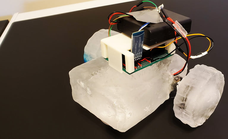 A rudimentary robot made out of blocks of ice with electronics attached.
