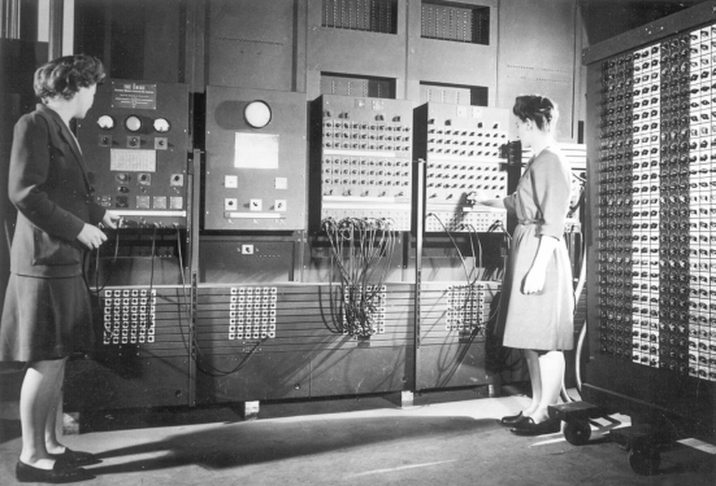 An archival photo of two women, Jean Bartik and Frances Spence, operating the ENIAC's main control panel, a massive, complicated array of dials and wires.