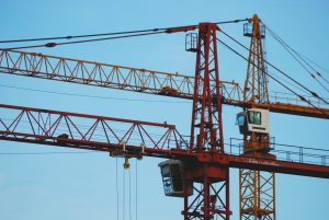Two red construction cranes against blue sky background