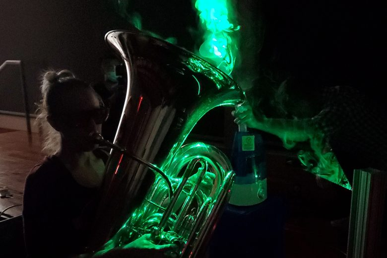 A tuba player bathed in neon green light, as the droplets coming out of the instrument are illuminated by a laser.
