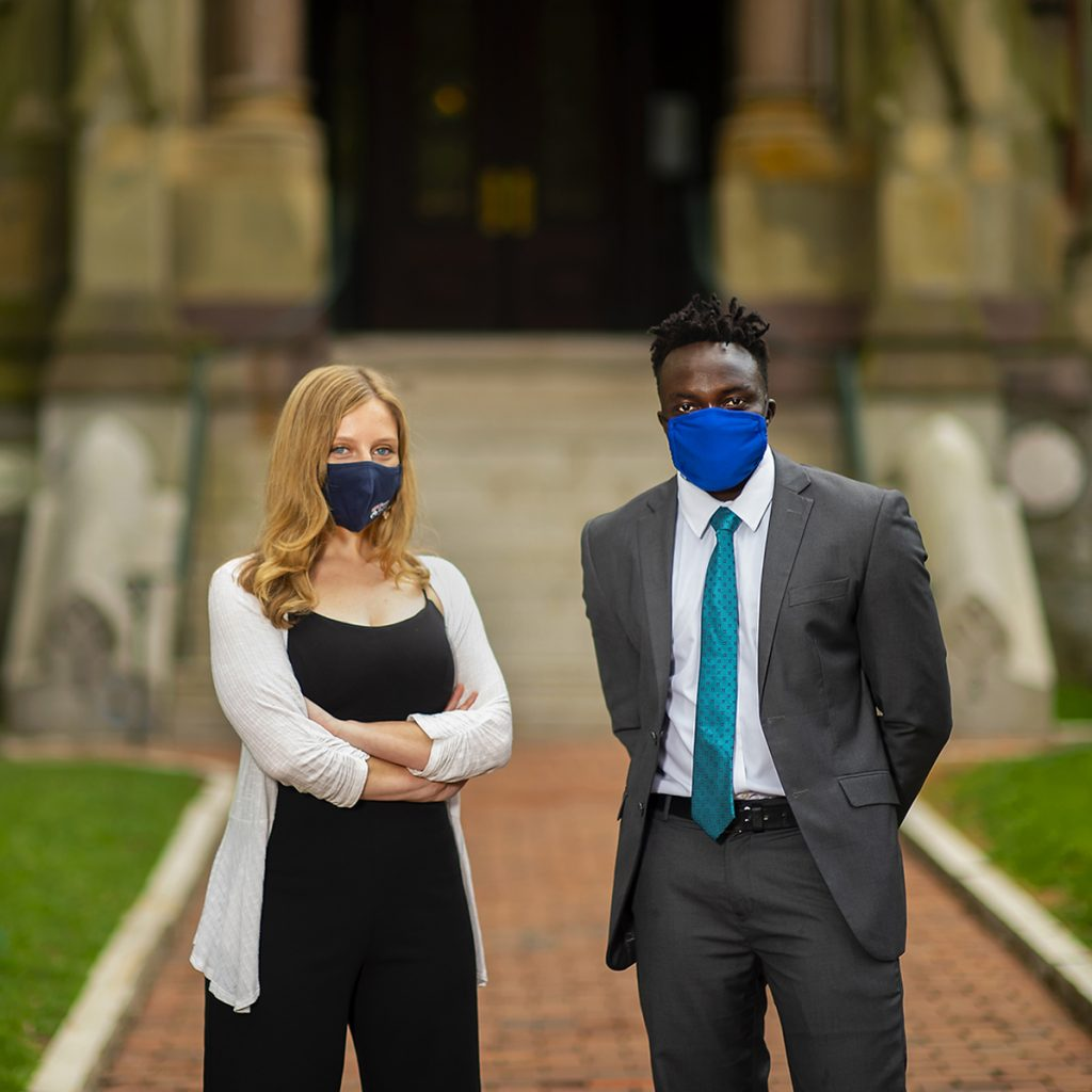 Leah Voytovich and Martin Leet stand in facemasks in front of College Hall.