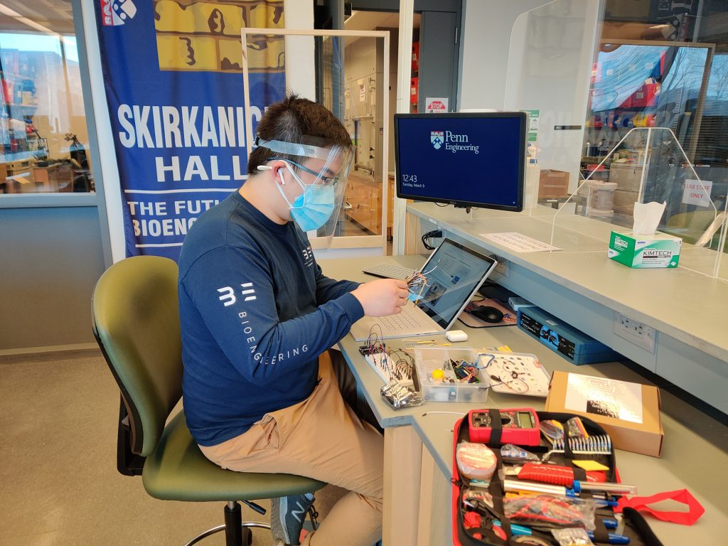 A student in a face mask and shield works at a lab bench covered with electronic equipment.