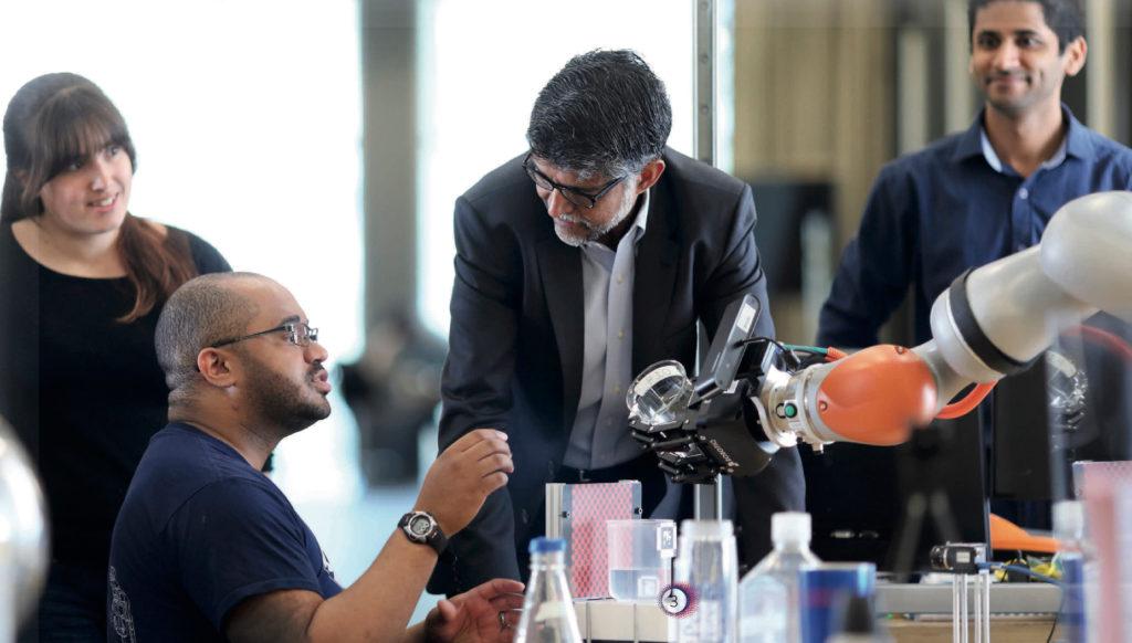 Dean Vijay Kumar works on a robotic arm with students