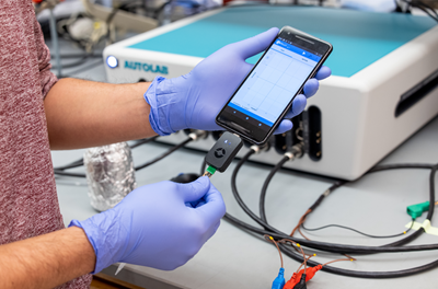 Close up gloved hands plugging a RAPID test into a smartphone.