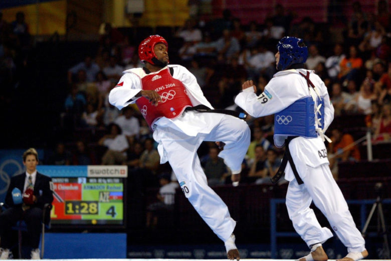 Chinedum Osuji delivers a kick in a taekwondo match at the 2004 Olympic Games