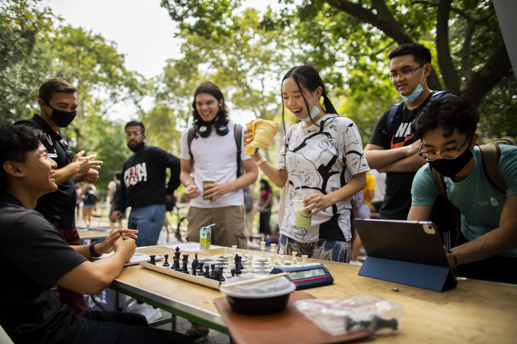 Students gather around a chessboard at an outdoor extracurricular fair.